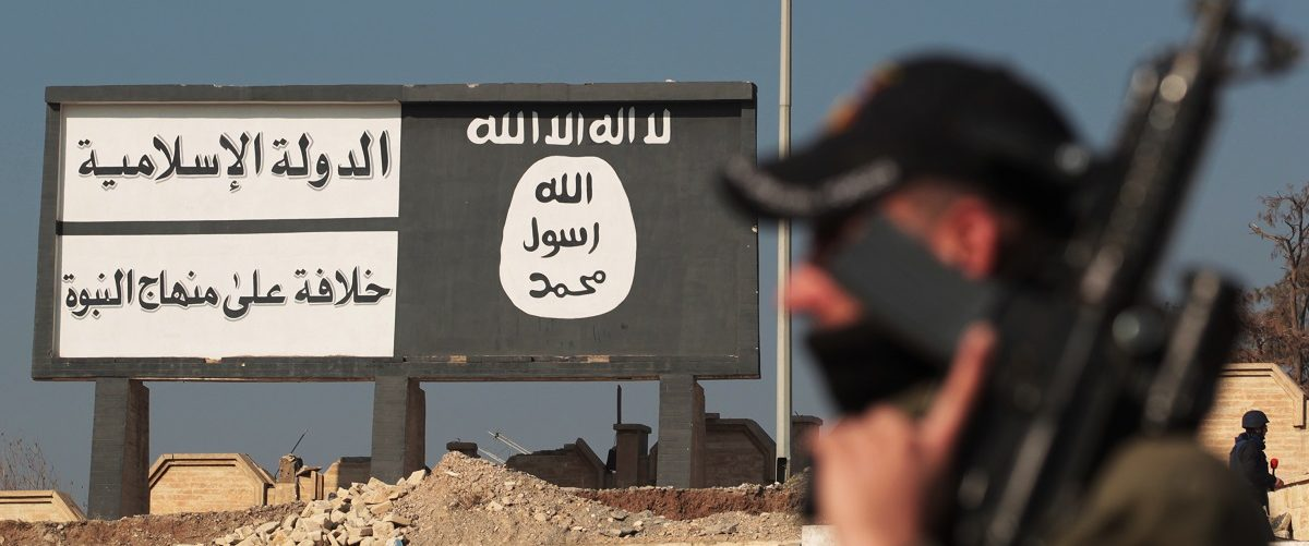A member of the special forces' Counter-Terrorism Service (CTS) stands in front of a billboard bearing the logo of the Islamic State (IS) group in Mosul's eastern district of Mohandessin on January 19, 2017, during an ongoing military operation against IS jihadists. Iraqi forces battled the last holdout jihadists in east Mosul after commanders declared victory there and set their sights on the city's west, where more tough fighting awaits. Ahmad Al-Rubaye/AFP/Getty Images.