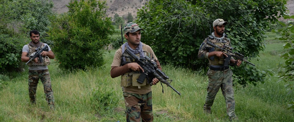 Afghan commando forces patrol at the site of US bombing in the Achin district of Nangarhar province on April 23, 2017.
