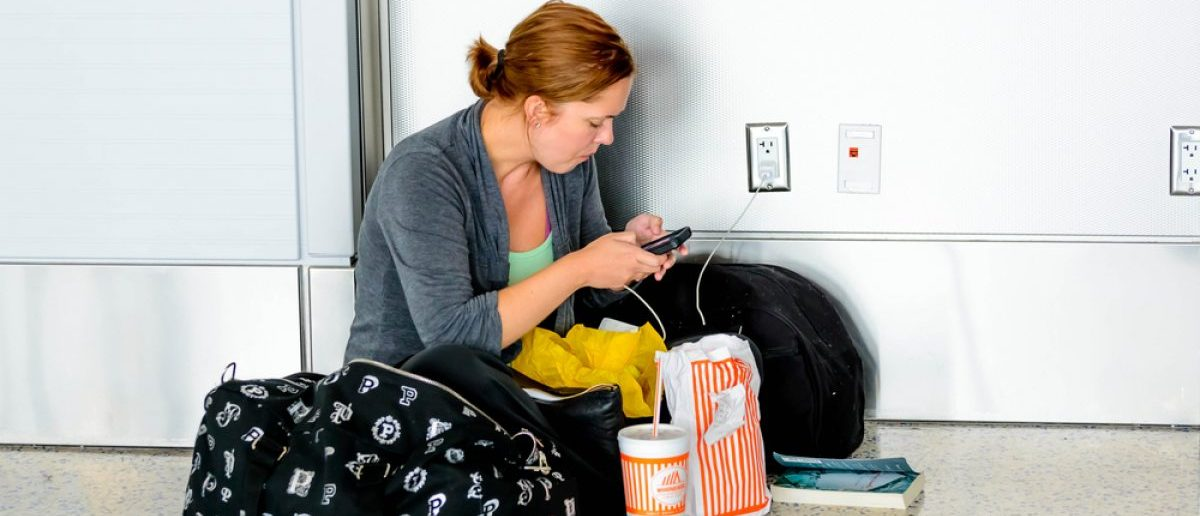 September 12, 2014: IAH, Houston Intercontinental Airport, Houston, TX, USA - Woman seated on the floor charging her phone in an airport. [Shutterstock - CaseyMartin]