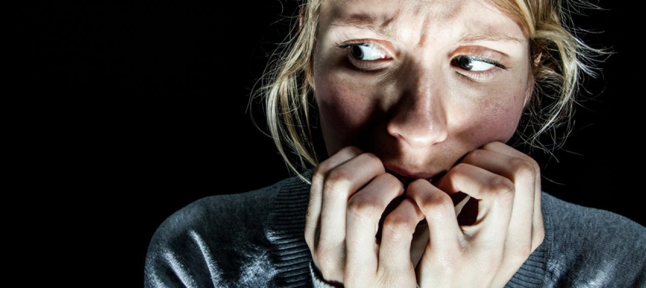 Scary Woman Afraid of something in the Dark (Shutterstock/Benoit Daoust)