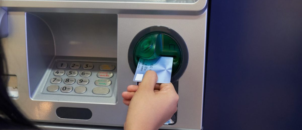 Woman inserting ATM card to conduct a financial transaction. [Shutterstock - pspn]