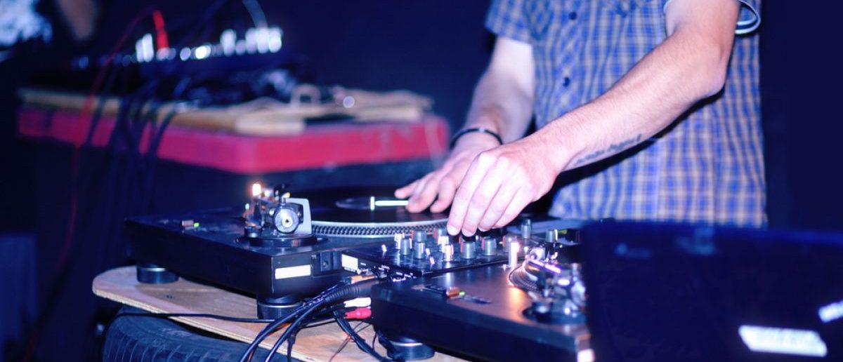 Disc Jockey [DJ] mixing tunes at a concert. [Shutterstock - Nicky Burton Photo]