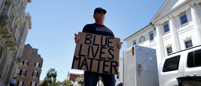 A lone Blue Lives Matter supporter holds a sign outside the Federal Courthouse before the Federal court hearing of former North Charleston police officer Michael Slager in Charleston, South Carolina May 2, 2017. REUTERS/Randall Hill
