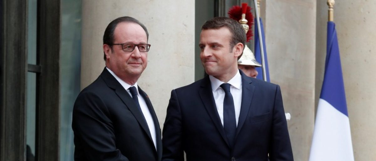 Outgoing French President Francois Hollande greets President-elect Emmanuel Macron who arrives to attend the handover ceremony at the Elysee Palace in Paris, France, May 14, 2017. REUTERS/Benoit Tessier