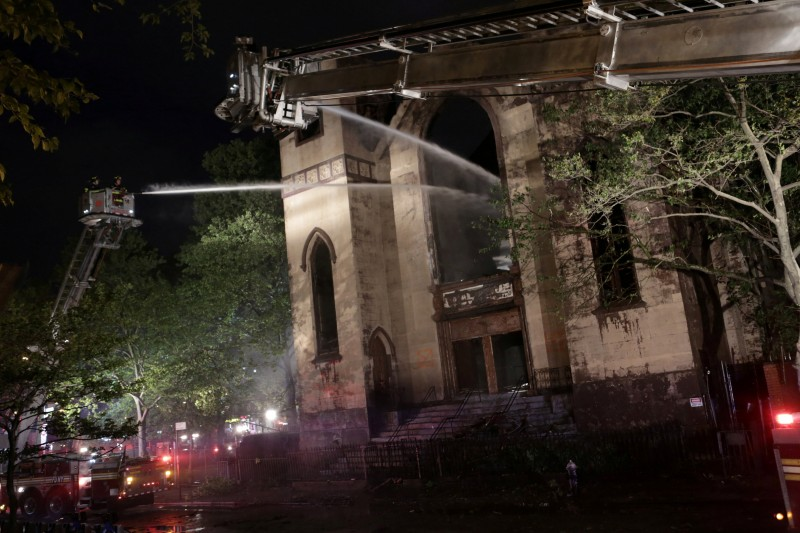FILE PHOTO: Firemen spray the burned Beth Hamedrash synagogue in New York City, U.S., on May 14, 2017. REUTERS/Joe Penney/File Photo