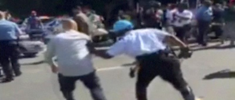 A police officer chases a protester, in this still image captured from a video footage, during a violent clash outside the Turkish ambassador's residence between protesters and Turkish security personnel during Turkish President Tayyip Erdogan's visit to Washington, DC, U.S. on May 16, 2017.   Courtesy Armenian National Committee of America/Handout via  REUTERS