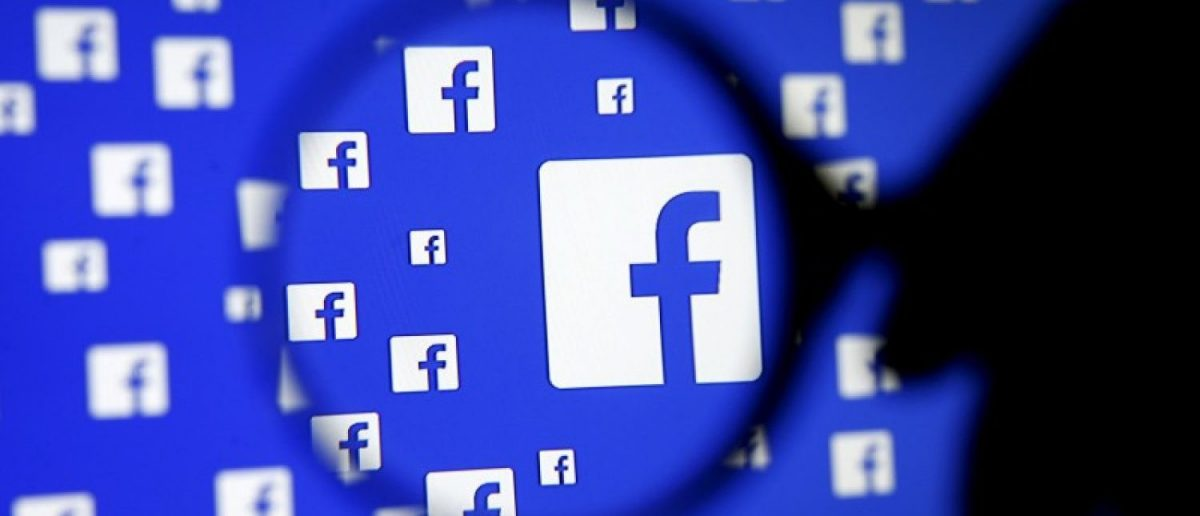 A man poses with a magnifier in front of a Facebook logo on display December 16, 2015. REUTERS/Dado Ruvic