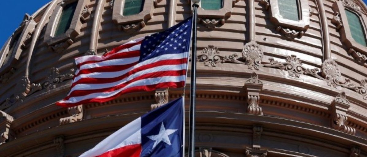 FILE PHOTO - The U.S flag and the Texas State flag fly over the Texas State Capitol in Austin, Texas, U.S. on March 14, 2017. REUTERS/Brian Snyder/File Photo