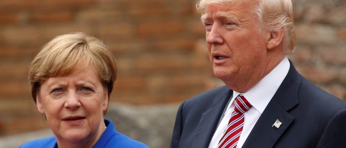 U.S. President Donald Trump and German Chancellor Angela Merkel pose during a family photo at the Greek Theatre during a G7 summit in Taormina, Sicily, Italy, May 26, 2017. REUTERS/Jonathan Ernst