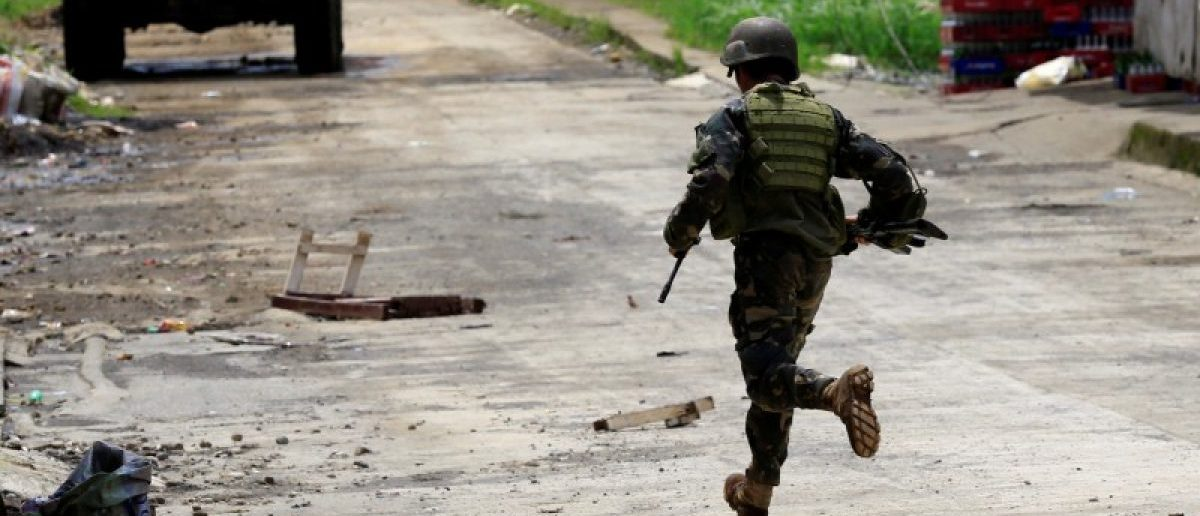 A government soldier runs towards his colleague. REUTERS/Romeo Ranoco