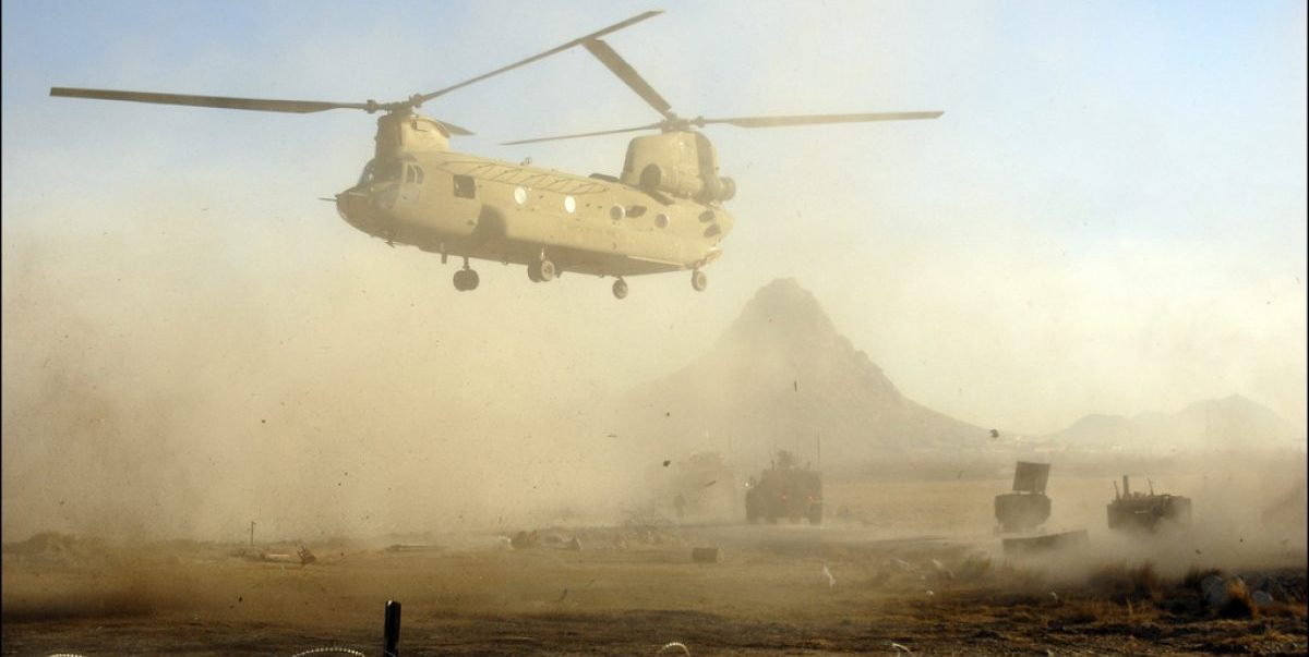 A Chinook helicopter passes over an International Security Assistance Forces convoy in order to drop soldiers off outside Combat Outpost Johnston Jan. 31, in the Arghandab District. Soldiers are frequently transported by air throughout the battle space in order to fill the slots of other soldiers going on leave.