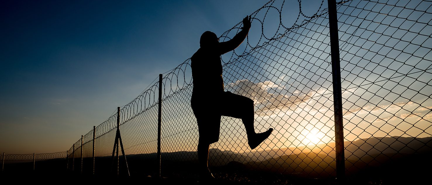 Man escapes over fence. (Akif Oztoprak/Shutterstock)