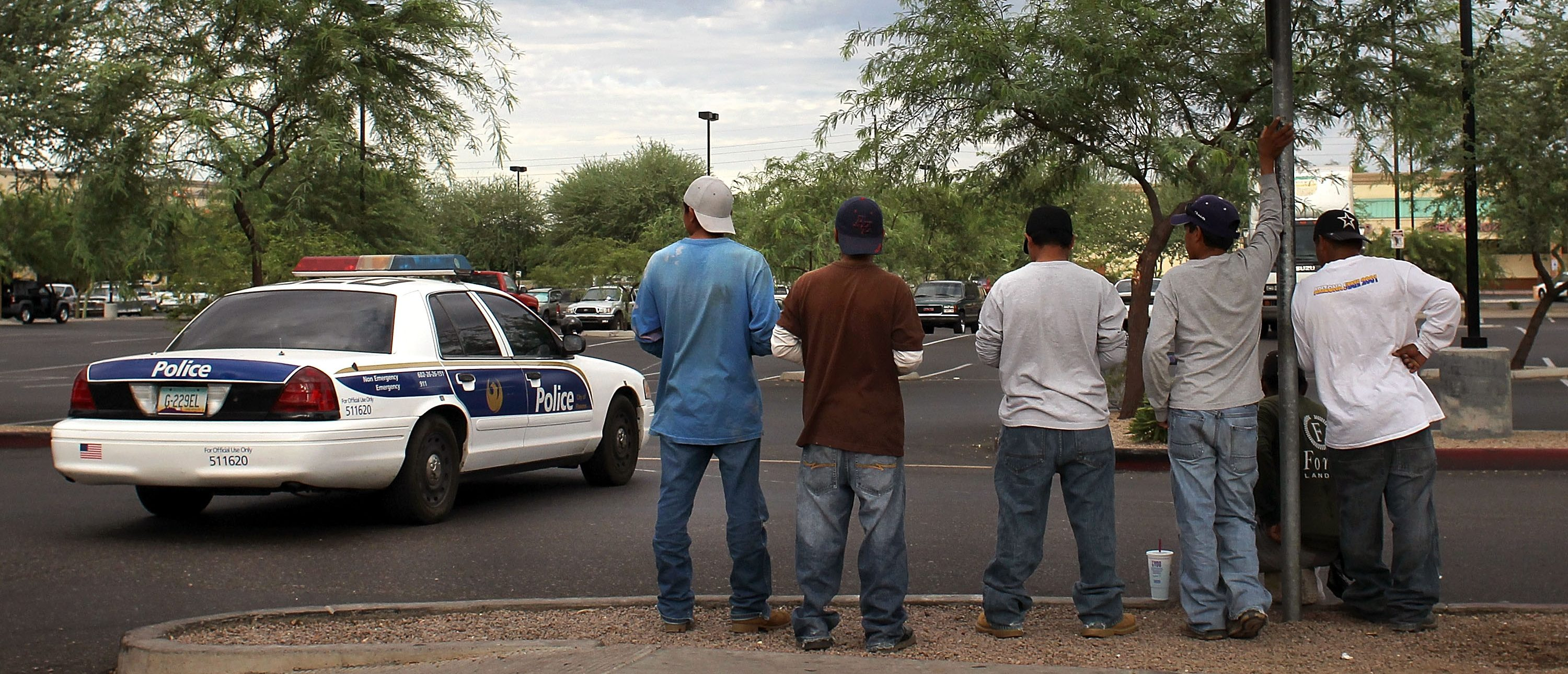 PHOENIX - JULY 26: Undocumented immigrants stand on a curbside awaiting day labor work as a police patrol passes by July 26, 2010 in Phoenix, Arizona. Arizona's new immigration enforcement law SB 1070 is due to go into effect Thursday and has caused widespread fear in the state's Latino community that Hispanics will be racially profiled by local police. In addition to criminalizing immigration status on a state level, the provision also makes it a crime for undocumented immigrants to