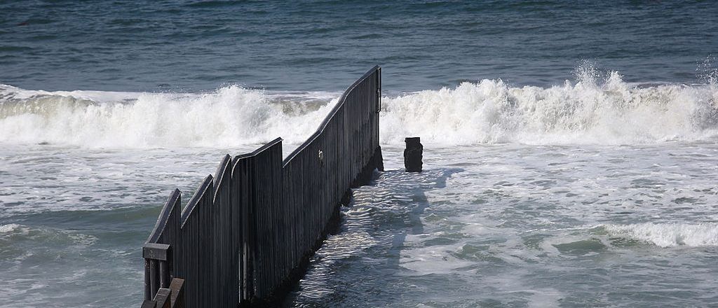 """SAN DIEGO, CA - OCTOBER 03: The western most tip of U.S.-Mexico border fence stretches into the Pacific Ocean on October 3, 2013 in San Diego, California. While hundreds of thousands of government workers were furloughed this week, thousands of Border Patrol agents, air-traffic controllers, prison guards and other federal employees deemed """"essential"""" remain on duty, although their pay may be delayed. (Photo by John Moore/Getty Images)"""