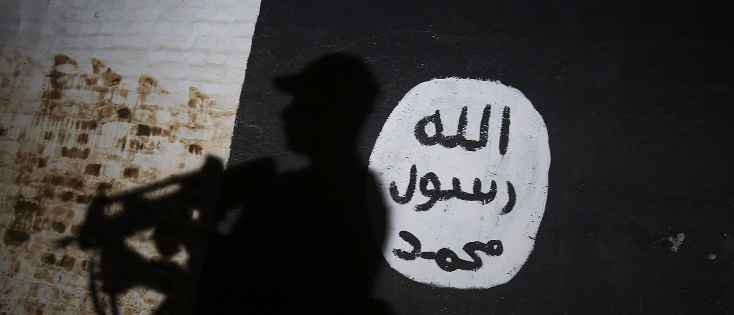 A member of the Iraqi forces walks past a mural bearing the logo of the Islamic State (IS) group. (PHOTO: AHMAD AL-RUBAYE/AFP/Getty Images)