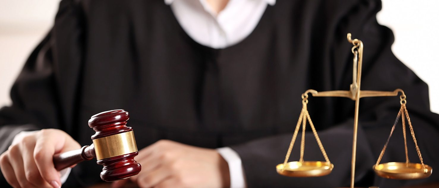 Judge hitting gavel at wooden table. (PHOTO: Africa Studio/Shutterstock)