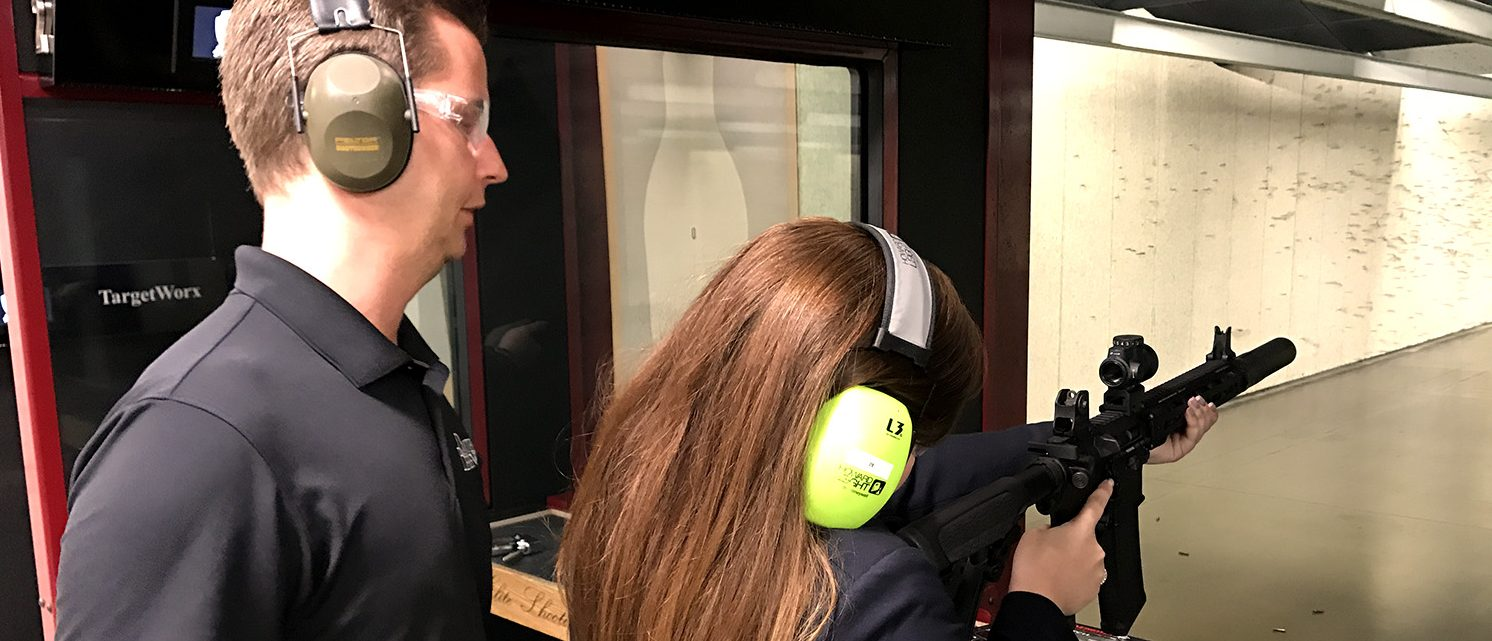 Lee Thompson, the product design director at Daniel Defense, shows Rachel Harris of The Herald Group how to shoot a suppressed rifle at Elite Shooting Sports in Manassas, Va. on May 22, 2017. (PHOTO: Will Racke/TheDCNF)