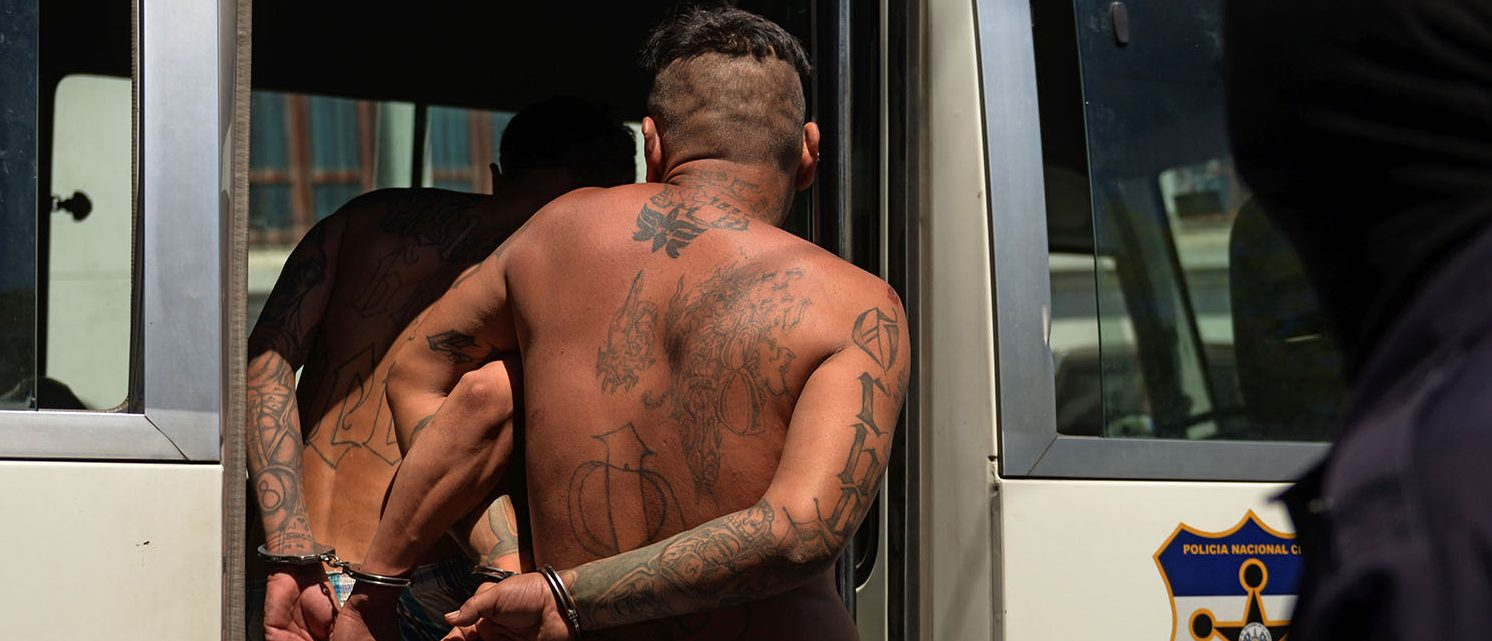 Alleged members of the MS13 and 18 gang board a police vehicle after being presented to the press in San Salvador on February 26, 2016. Members of the national civil police and the armed forces captured 240 dangerous gang members accused of homicide and extortion in the last three days in different areas of El Salvador, informed Friday the public prosecutor's office. El Salvador faces an escalation of violence attributed mostly to the war between the MS-13 and 18 ST gangs. AFP (PHOTO: Marvin RECINOS / AFP / Getty Images)