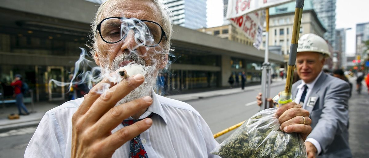 Activist Ray Turmel holds a bag of medical marijuana while he smokes a marijuana cigarette, as he calls for the total legalization of marijuana, outside the building where the federal election Munk Debate on Canada's Foreign Policy is being held in Toronto, Canada, September 28, 2015. REUTERS/Mark Blinch