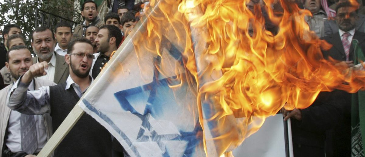 Jordanian demonstrators burn a flag with the Star of David in Amman March 16, 2010 during a protest against Israel's consecration of a synagogue in Jerusalem's Old City. REUTERS/Muhammad Hamed