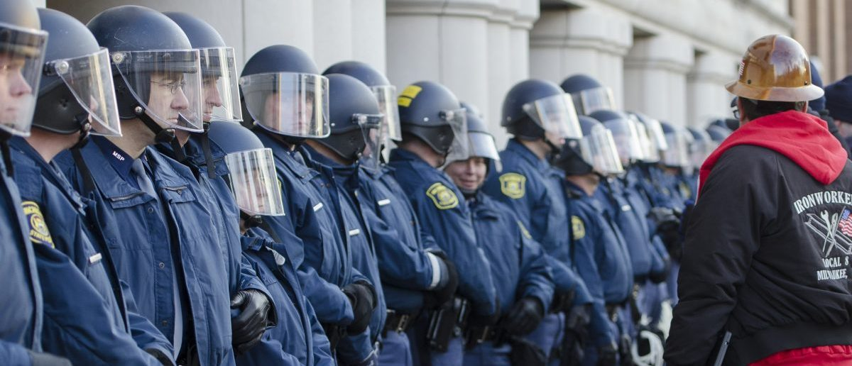 Police in riot gear block the perimeter of the George W. Romney State Office Building across from the Capitol as labor union members and supporters demonstrate in opposition to a right-to-work measure in Lansing, Michigan December 11, 2012. Michigan legislators on Tuesday approved laws that ban mandatory membership in public and private sector unions, dealing a stunning blow to organized labor in the home of the U.S. auto industry. REUTERS/James Fassinger