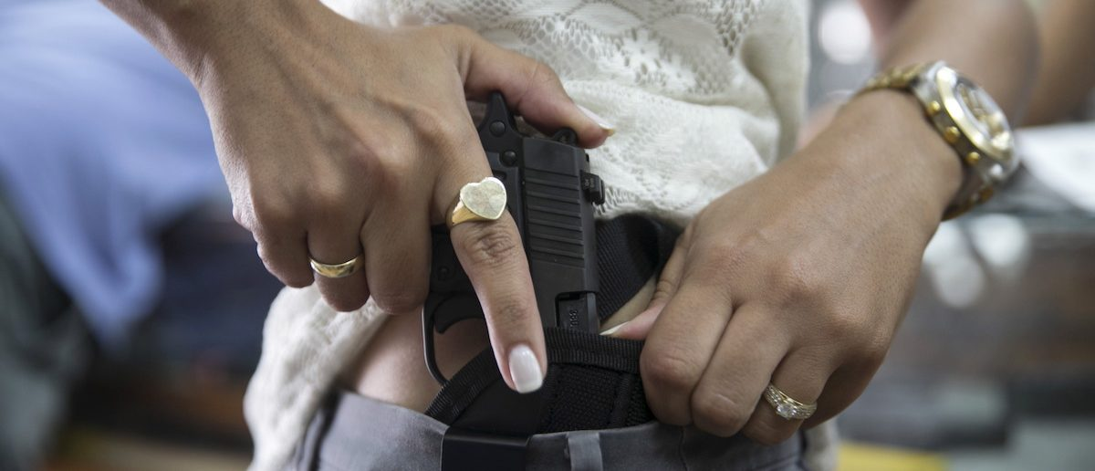 An Israeli woman checks out a new pistol at a gun shop in Tel Aviv October 20, 2015. A growing number of Israelis are attending self defence classes, learning how to protect themselves from knife attacks, as the country has seen near-daily stabbings and shootings by Palestinians and Israeli-Arabs. Many people have also rushed to gun shops and shooting ranges to get a weapon or renew their existing gun license. REUTERS/Baz Ratner TPX IMAGES OF THE DAY - RTS5AJI