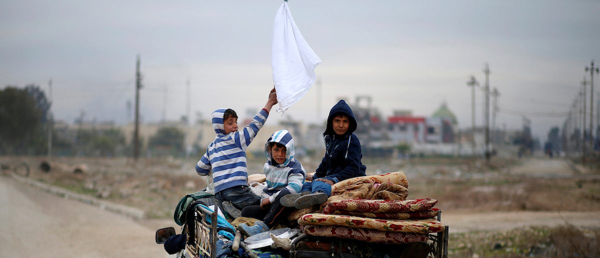 A displaced Iraqi boy holds a white flag as his family flees during the battle between Iraqi rapid response forces and Islamic State militants at Tigris river frontline between east and west of Mosul , Iraq, January 25, 2017. REUTERS/Ahmed Jadallah TPX IMAGES OF THE DAY - RTSXB7T