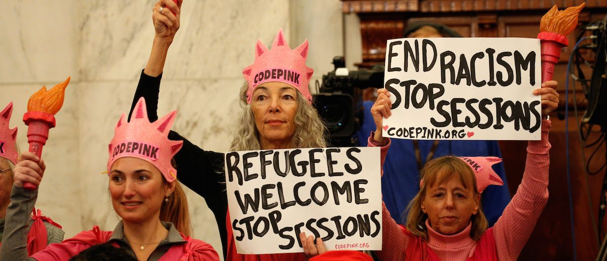 Desiree Fairooz, center, and other Code Pink protestors hold signs at Jeff Sessions confirmation hearing to become U.S. attorney general Jan. 10, 2017 (Photo: REUTERS/Kevin Lamarque)