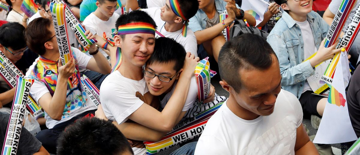 Supporters hug each other during a rally after Taiwan's constitutional court ruled that same-sex couples have the right to legally marry, the first such ruling in Asia, in Taipei, Taiwan May 24, 2017. REUTERS/Tyrone Siu TPX IMAGES OF THE DAY - RTX37CD8