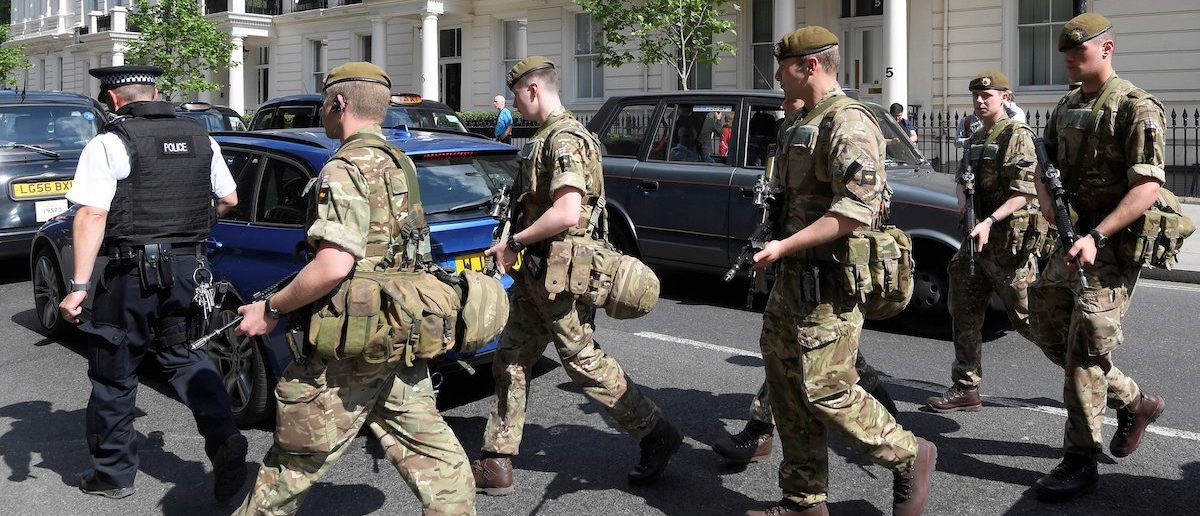 Soldiers cross a road with a police officer in central London, Britain May 24, 2017. REUTERS/Toby Melville - RTX37F1E