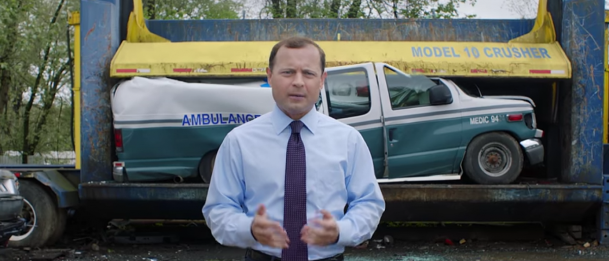 Perriello stand in front of a crushed ambulance Youtube screengrab