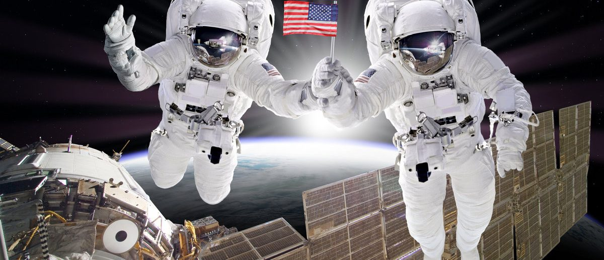 Astronauts floats on space sunrise holding USA flag. Artist creative edit composite depicting activities on International Space station. Elements of this image furnished by NASA. (Shutterstock/Alexlky)