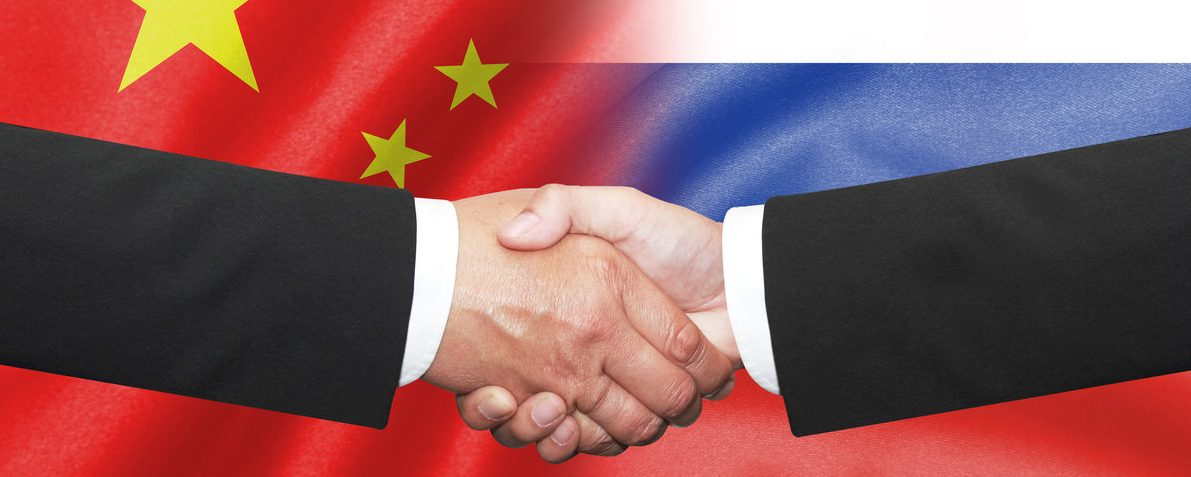 Two business man shakehand on china and russian flag (Shutterstock/charnsitr)