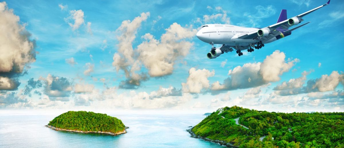 Jet flying over a remote island and ocean. [Shutterstock - MO_SES Premium]