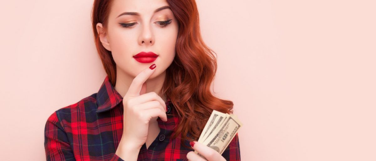 Woman looks quizzically at money (Shutterstock/Masson)