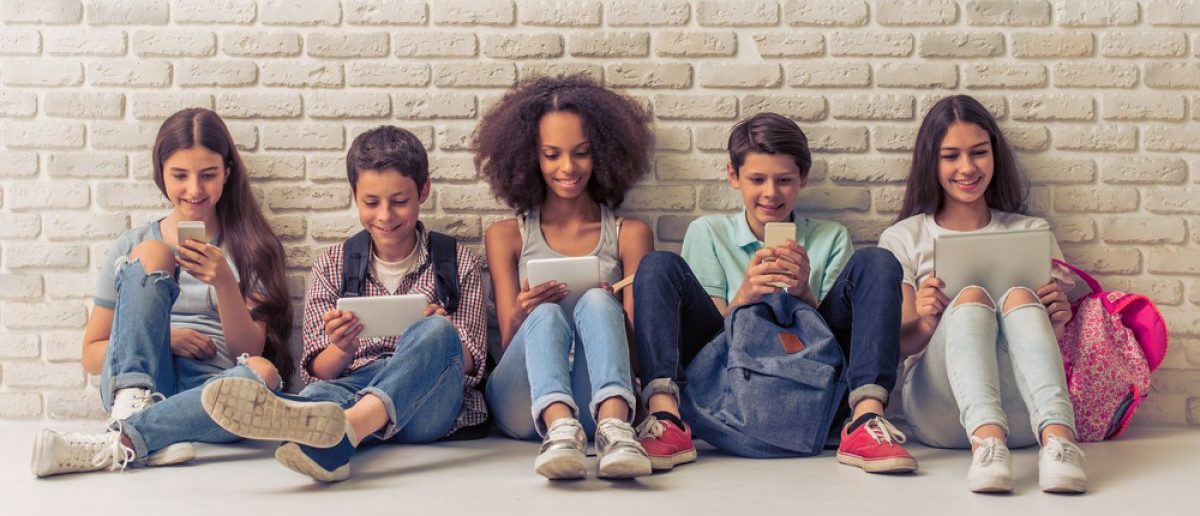 A group of teenage boys and girls using gadgets and smiling. [Shutterstock - George Rudy]