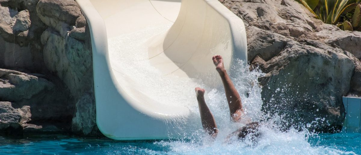 Splashes of water left by a kid in a pool with a water slide. [Shutterstock - Olga Lipatova]