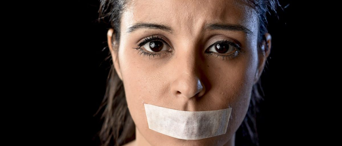 Woman with mouth taped shut (Shutterstock/Marcos Mesa Sam Wordley)