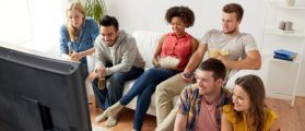 Friends watching a movie with subtitles. [Shutterstock - Syda Productions]