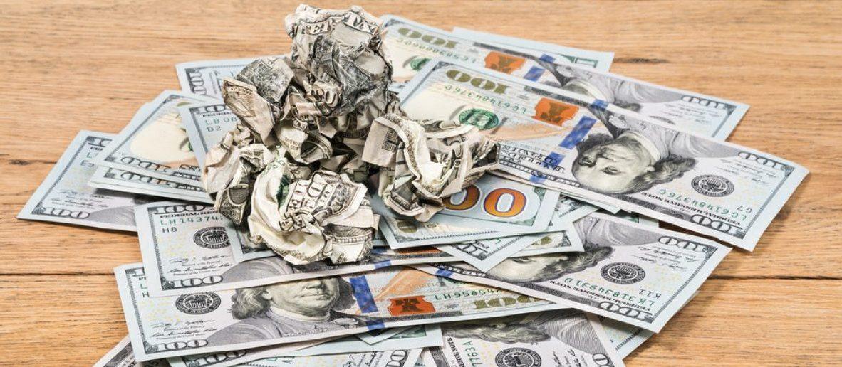 Crumpled money on a pile of new $100 dollar bills.  [Shutterstock - GrashAlex]