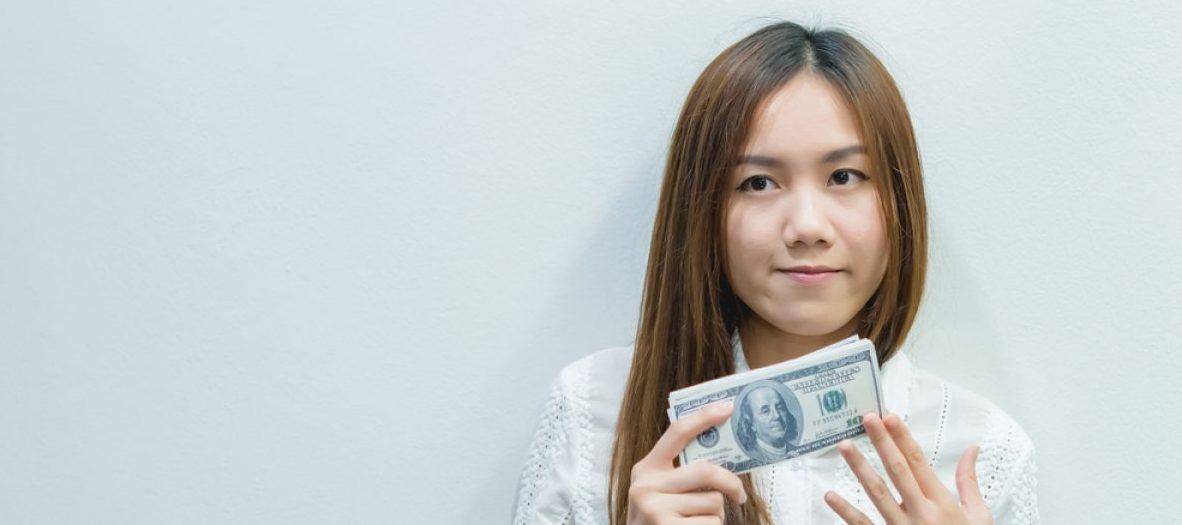 Woman holding money (Shutterstock/kittirat roekburi)