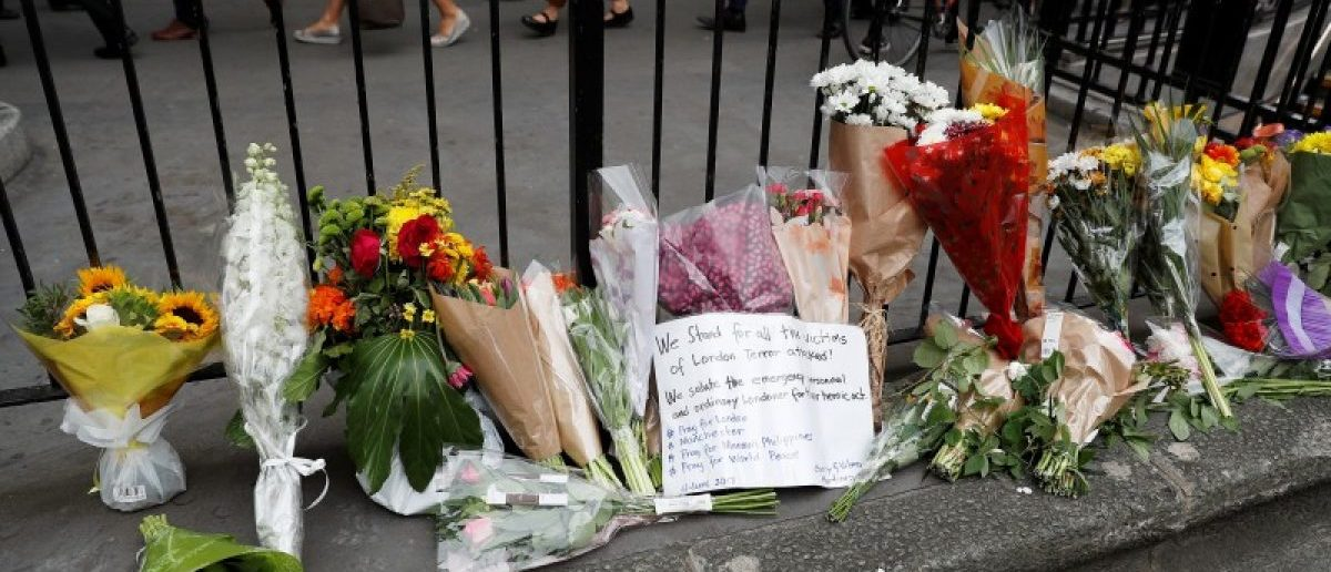 Commuters walk past flowers and messages left outside Monument Underground station next to London Bridge following an attack which left 7 people dead and dozens of injured in central London, Britain, June 5, 2017. REUTERS/Peter Nicholls