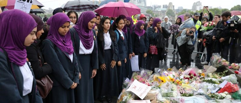 School girls look at floral tributes after a vigil to remember the victims of the attack on London Bridge and Borough Market, at Potters Field Park, in central London, Britain, June 5, 2017. REUTERS/Marko Djurica