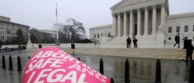 A woman holds a sign in the rain as abortion rights protesters arrive to prepare for a counter protest against March for Life anti-abortion demonstrators on the 39th anniversary of the Roe vs Wade decision, in front of the U.S. Supreme Court building in Washington, January 23, 2012. REUTERS/Jonathan Ernst/File Photo