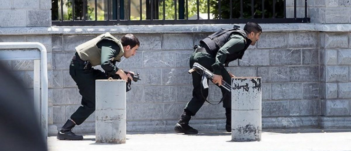 Members of Iranian forces take cover during an attack on the Iranian parliament in central Tehran, Iran, June 7, 2017. Tasnim News Agency/Handout via REUTERS