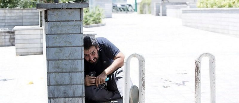 A man takes cover during an attack on the Iranian parliament in central Tehran, Iran. Tasnim News Agency/Handout via REUTERS