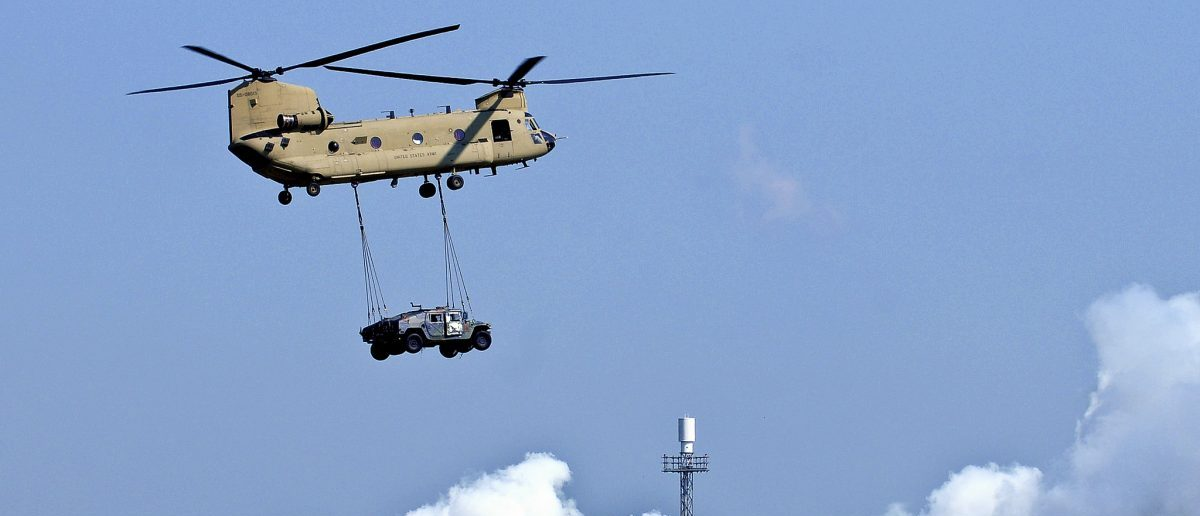 Two Humvees dangle below a CH-47 Chinook during a sling load demonstration at Campbell Army Airfield Tuesday. This demonstration was a rehearsal for the air assault that will occur Saturday as part of the Fort Campbell Air Show, which begins at 10 a.m.
