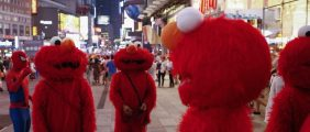 Jorge, an immigrant from Mexico (C), stands amidst other people, all dressed as the Sesame Street character Elmo, while they look to make tips for photographs in Times Square in New York July 30, 2014. Elmo and Cookie Monster have long delighted young viewers on TV's