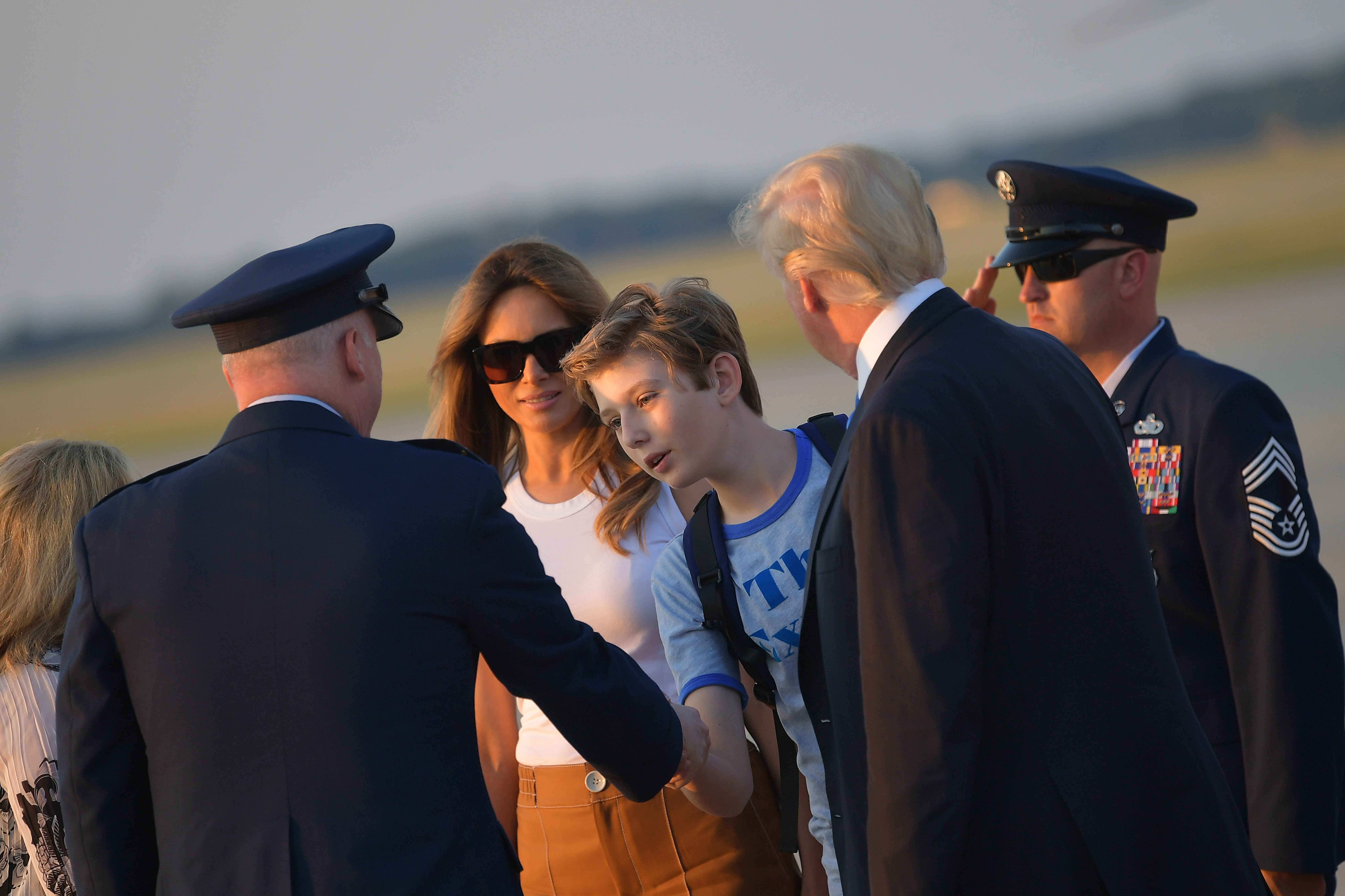 First Lady Melania Trump (2L) and US President Donald Trump (2R) watch as their son Barron Trump shakes hands with Col Al Smith who greeted them upon arrival at Andrews Air Force Base in Maryland on June 11, 2017. Trump is returning to Washington, DC after spending the weekend at this Bedminster, New Jersey golf club. MANDEL NGAN/AFP/Getty Images