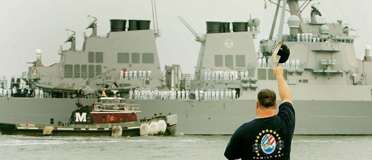 NORFOLK, VA - JUNE 08: A well wisher waves goodbye to the USS Cole as a tug boat guides it away from the dock at the Norfolk Naval Station.  (Photo by Mark Wilson/Getty Images)